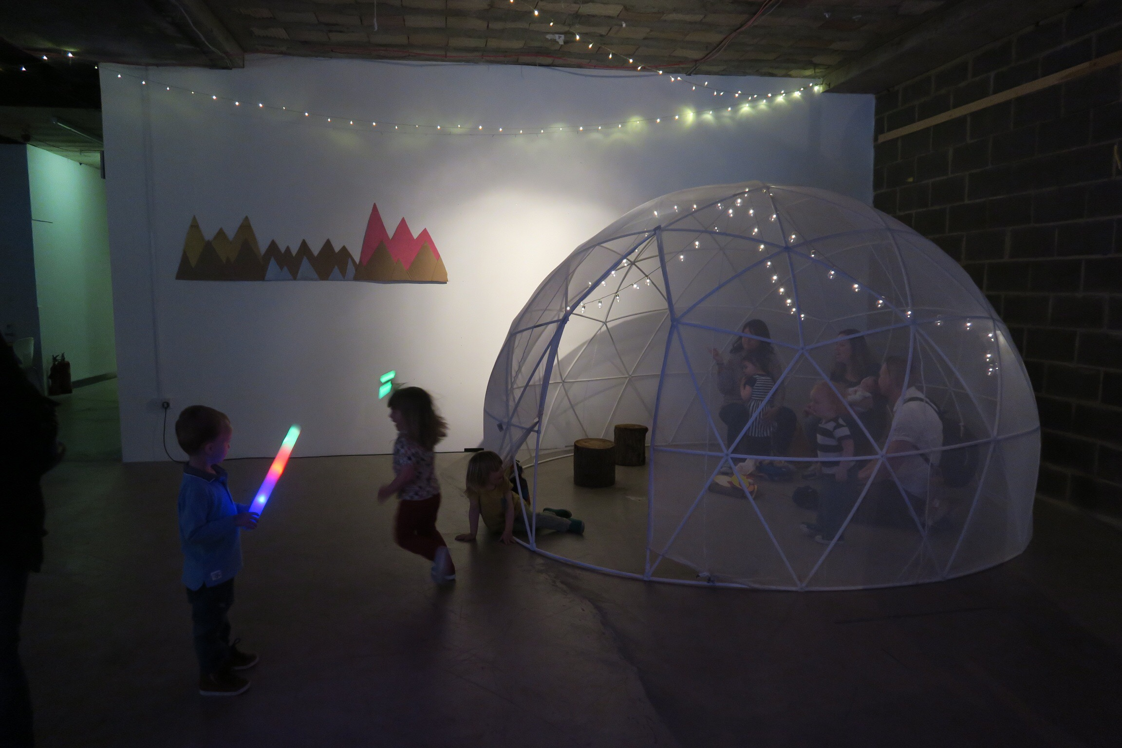 arlo playing with his rave light saber near the igloo