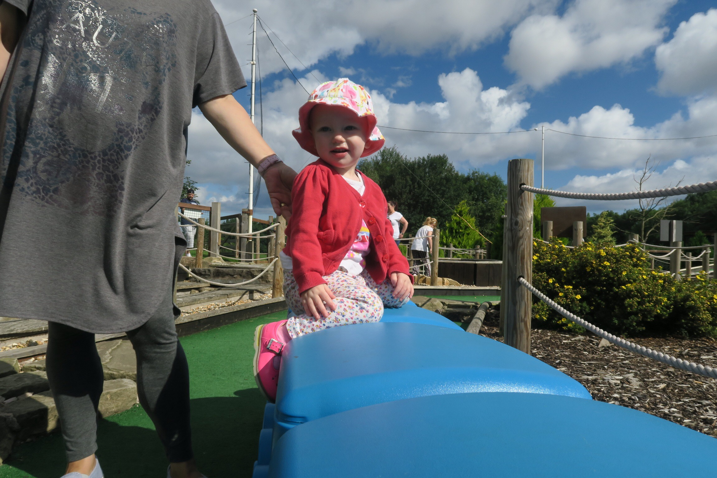 A toddler climbing at mini golf at Haggerston Castle Holiday Park