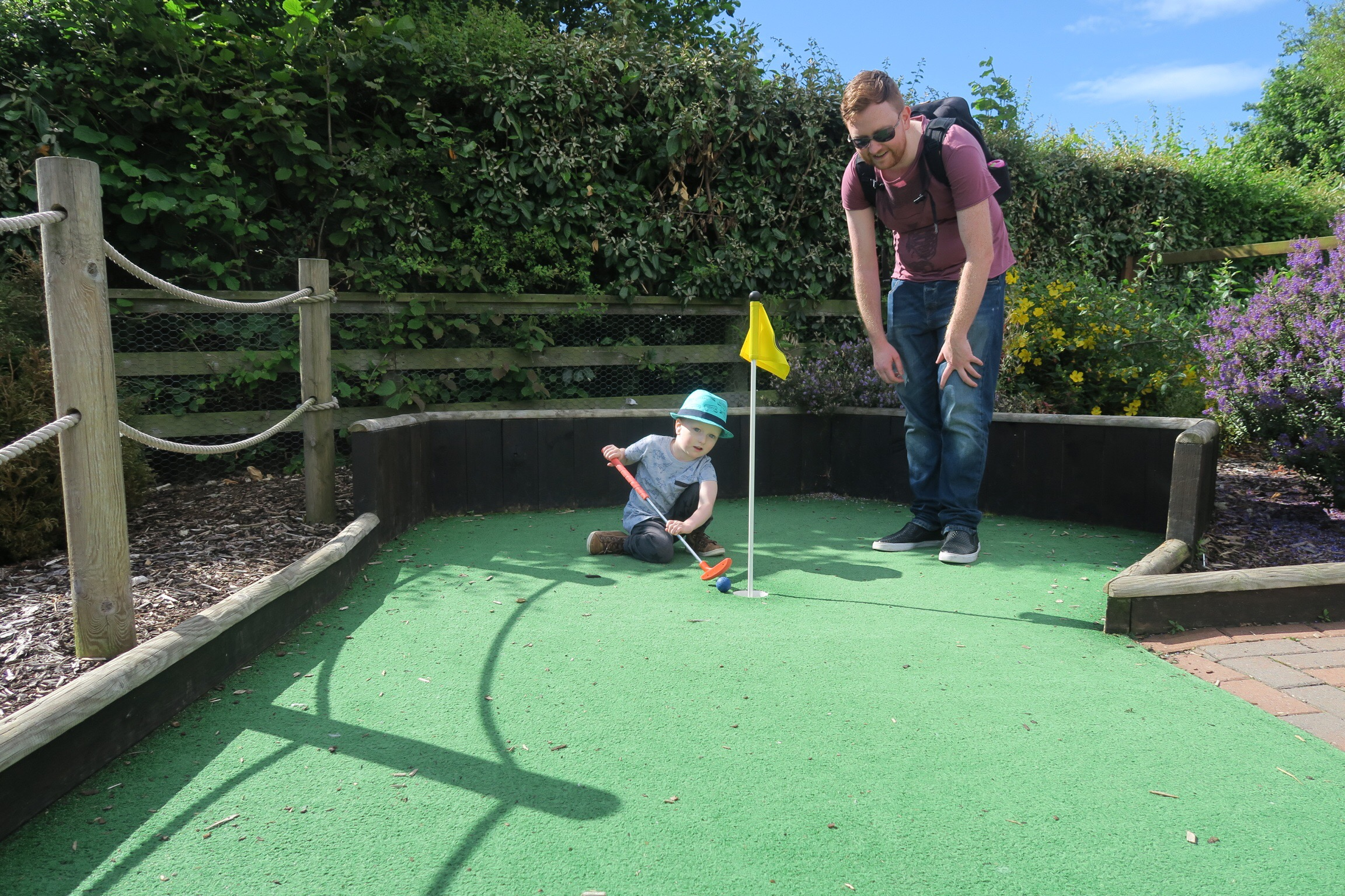 A father and son playing mini golf at Haggerston Castle Holiday Park