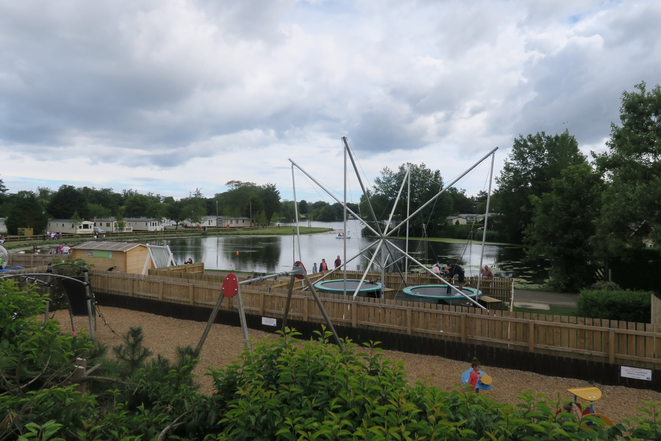 One of the play areas at Haggerston Castle - a playground and two trampolines next to a boating lake.