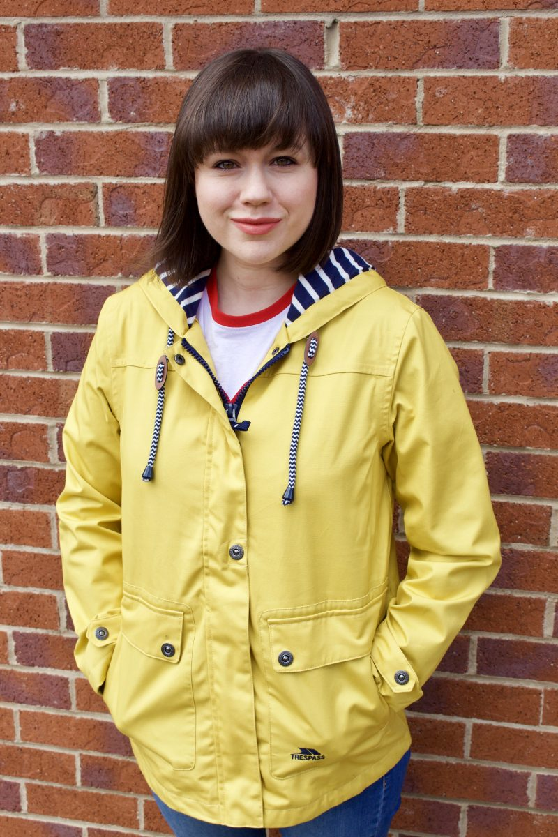 A brunette woman smiles at the camera wearing a yellow Tresspass Seawater jacket. You can see blue and white striped toggles and inner hood lining.