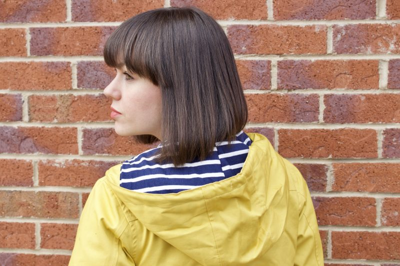 A brunette woman has her back to the camera, she is wearing a yellow Tresspass Seawater jacket with a blue and white striped inner hood.