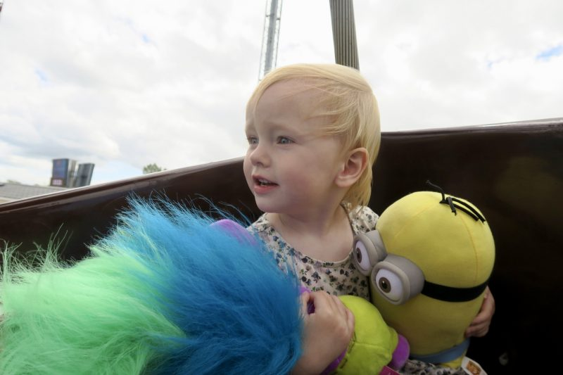 A toddler holding a trolls and minions stuffy that we won from the Flamingo Land grabbers
