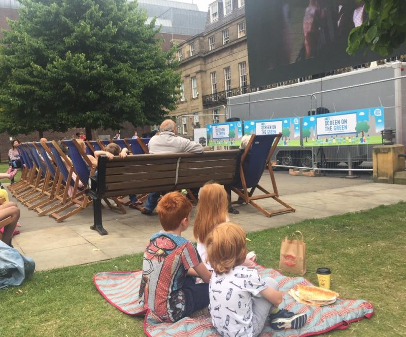 3 children watch a movie with a picnic at screen on the green at Newcastle city centre