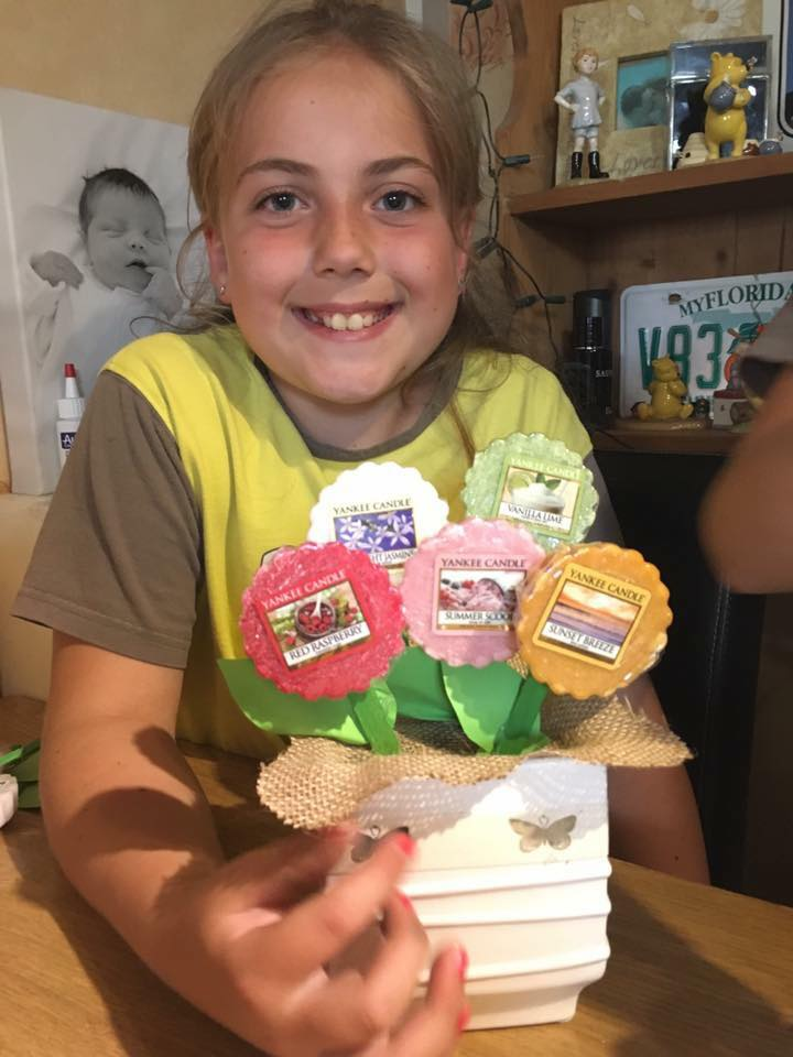 A little girl smiling holding a homemade Yankee candle flower pots gift for her teacher