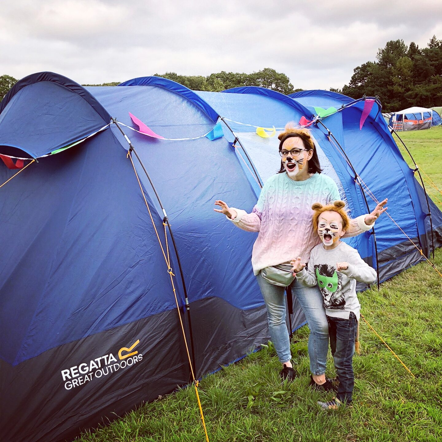 Woman and child wearing lion face faints, pretending to roar whilst stood in front of a blue tent with rainbow coloured bunting.