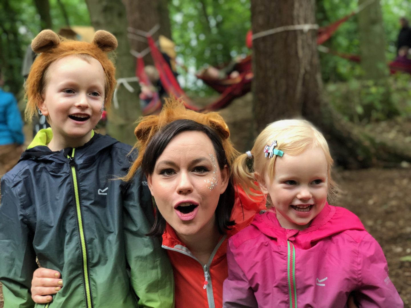 A woman and a boy and a girl and all posing for a photo together and are laughing. They are clearly at a festival and are wearing waterproof jackets.