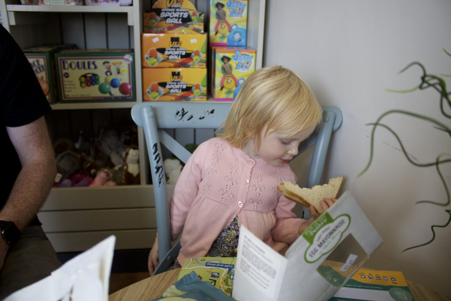 Little girl wearing a pink cardigan eating a sandwich in a cafe