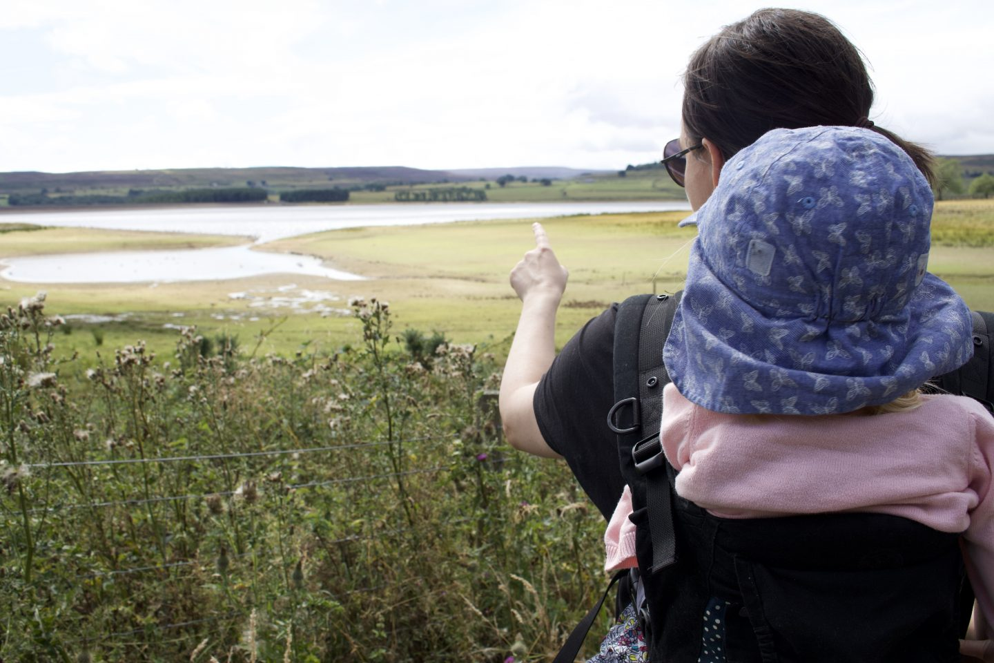 A woman carrying a toddler in a baby carrier on her back whilst pointing at the reservoir