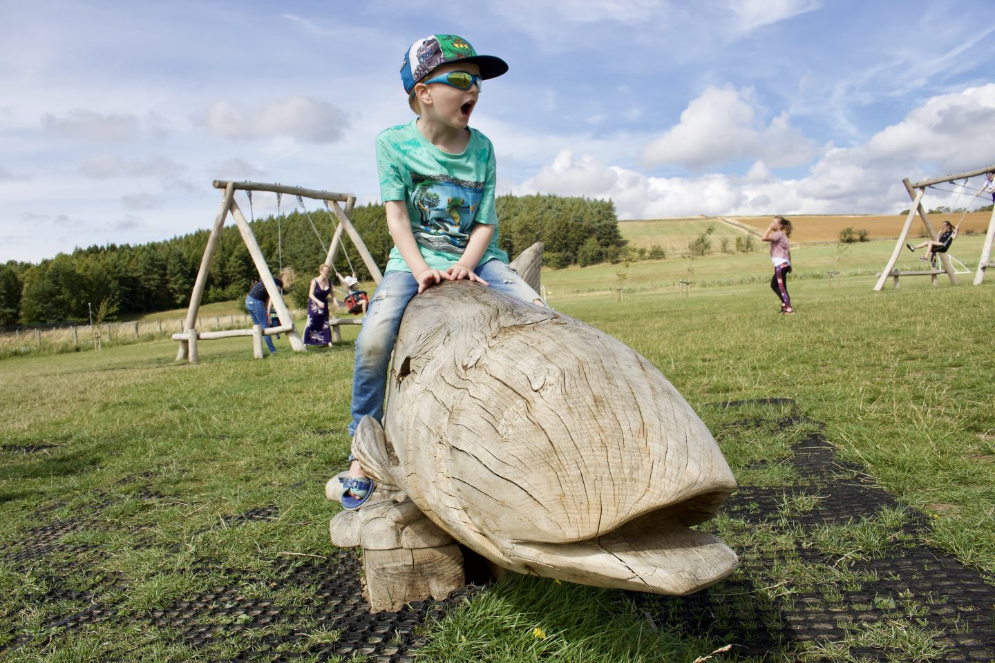 A young boy pretending to ride a large wooden whale