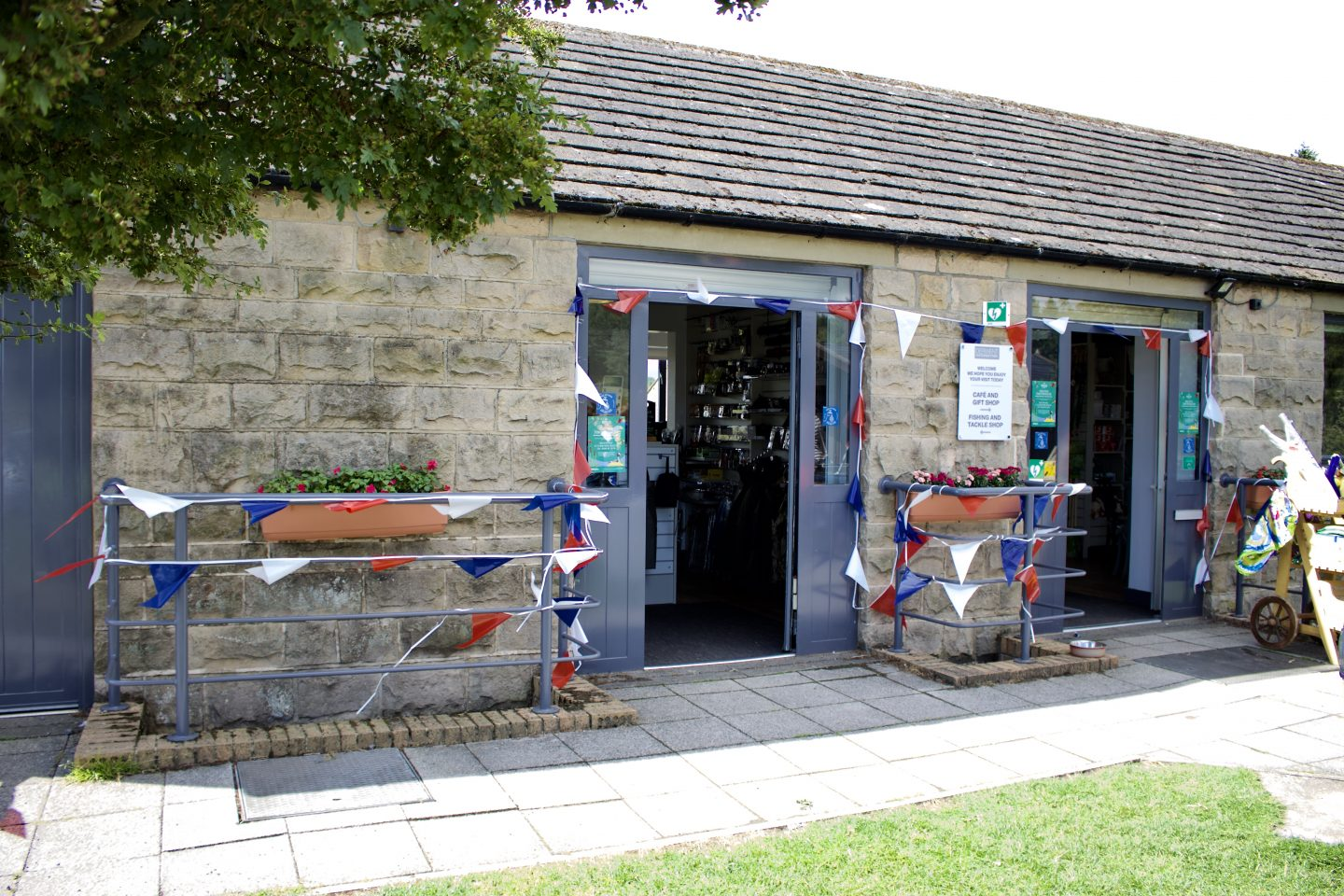 A photo of the outside of the cafe - a stone building with red, white and blue bunting