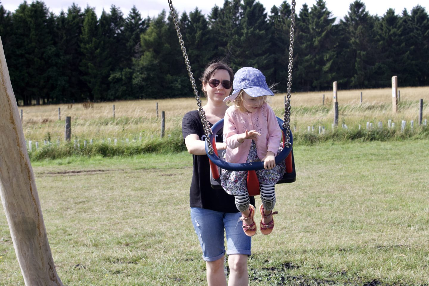 A brunette woman smiling pushing her daughter on a swing