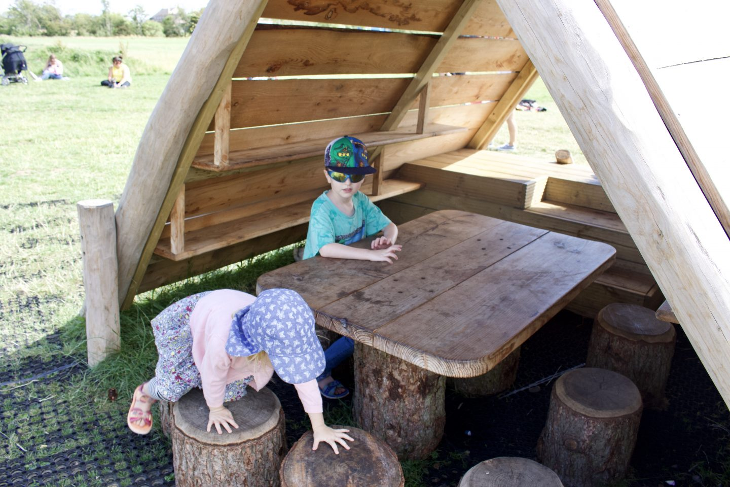 Two children playing at a wooden table and stools
