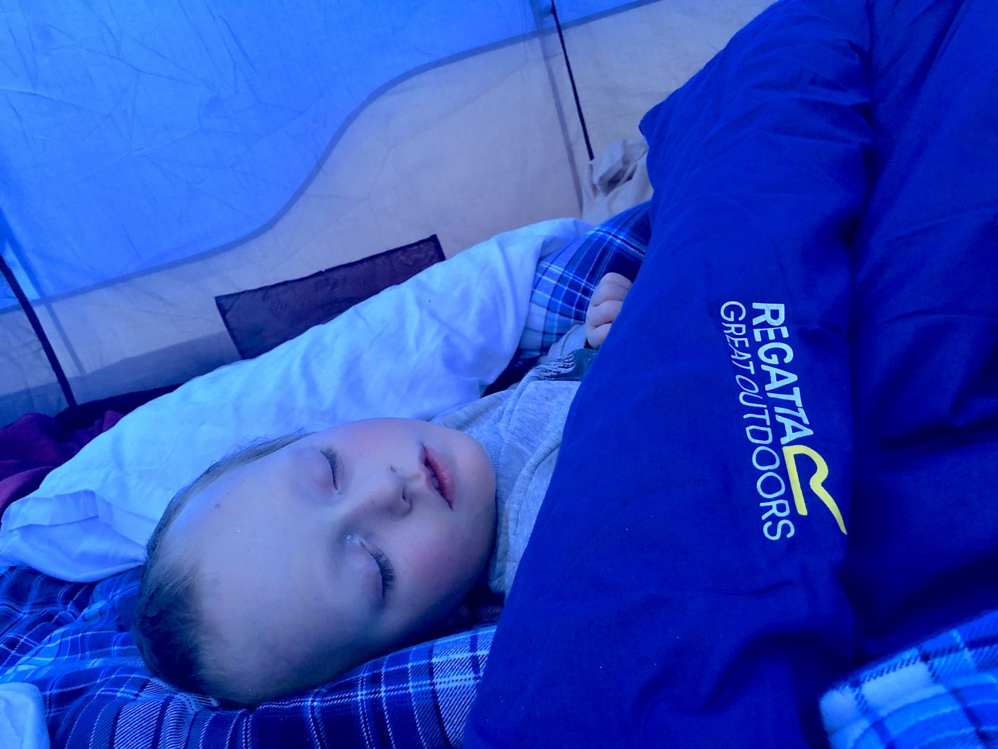 A young boy fast asleep inside his sleeping bag in a tent.