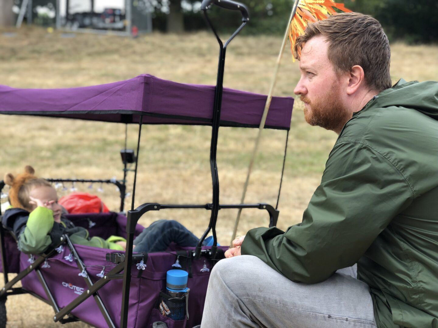 A boy lounges in a festival wagon for kids as his father stares off into the distance.