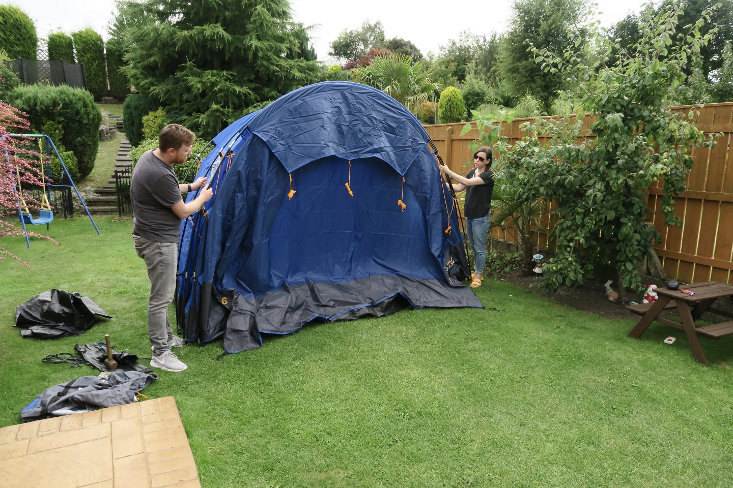 Man and woman putting up a large blue tent in a garden