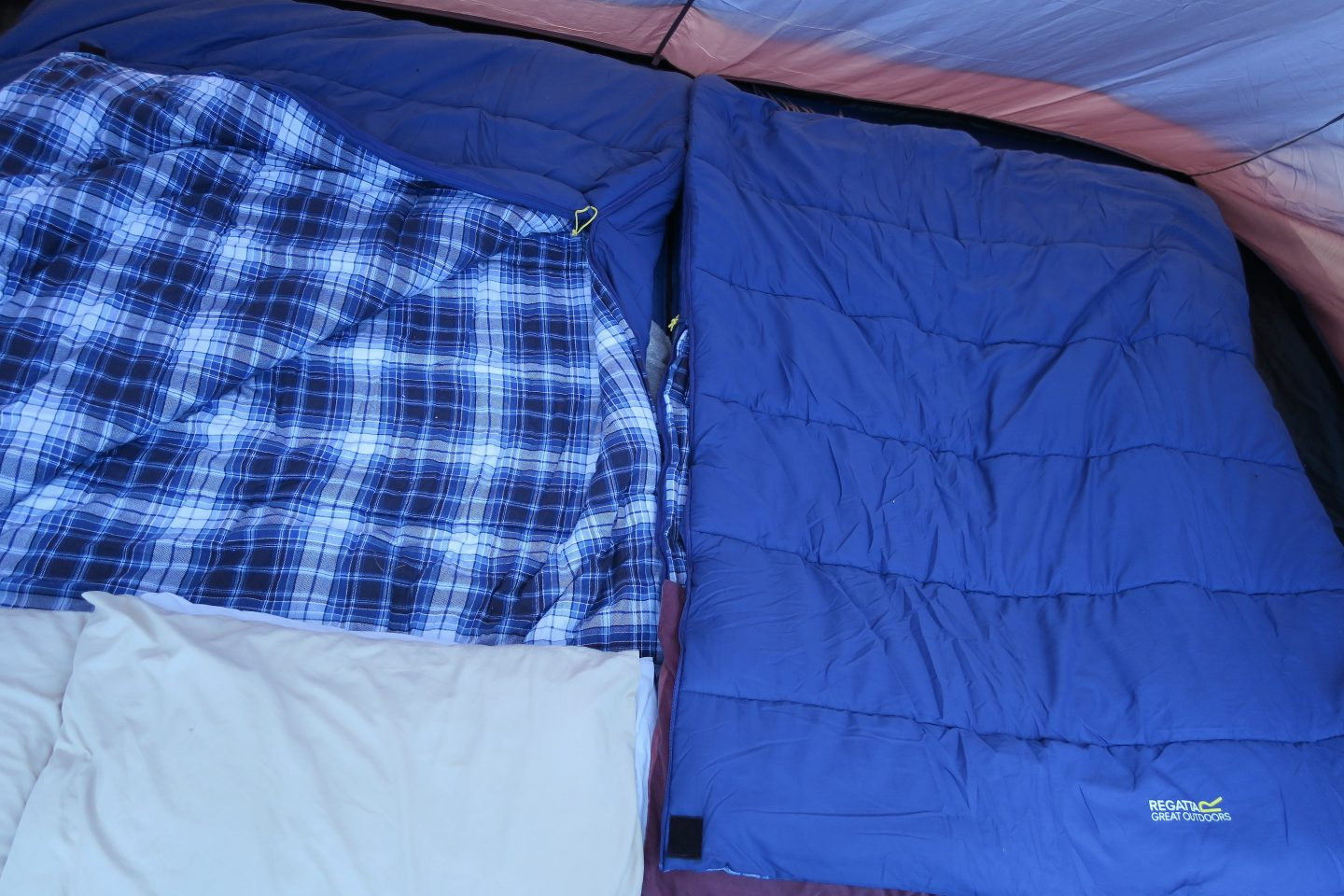 The bedroom set up inside a tent. Shows two double sleeping bags next to each other. They are blue and the inside is a blue check.
