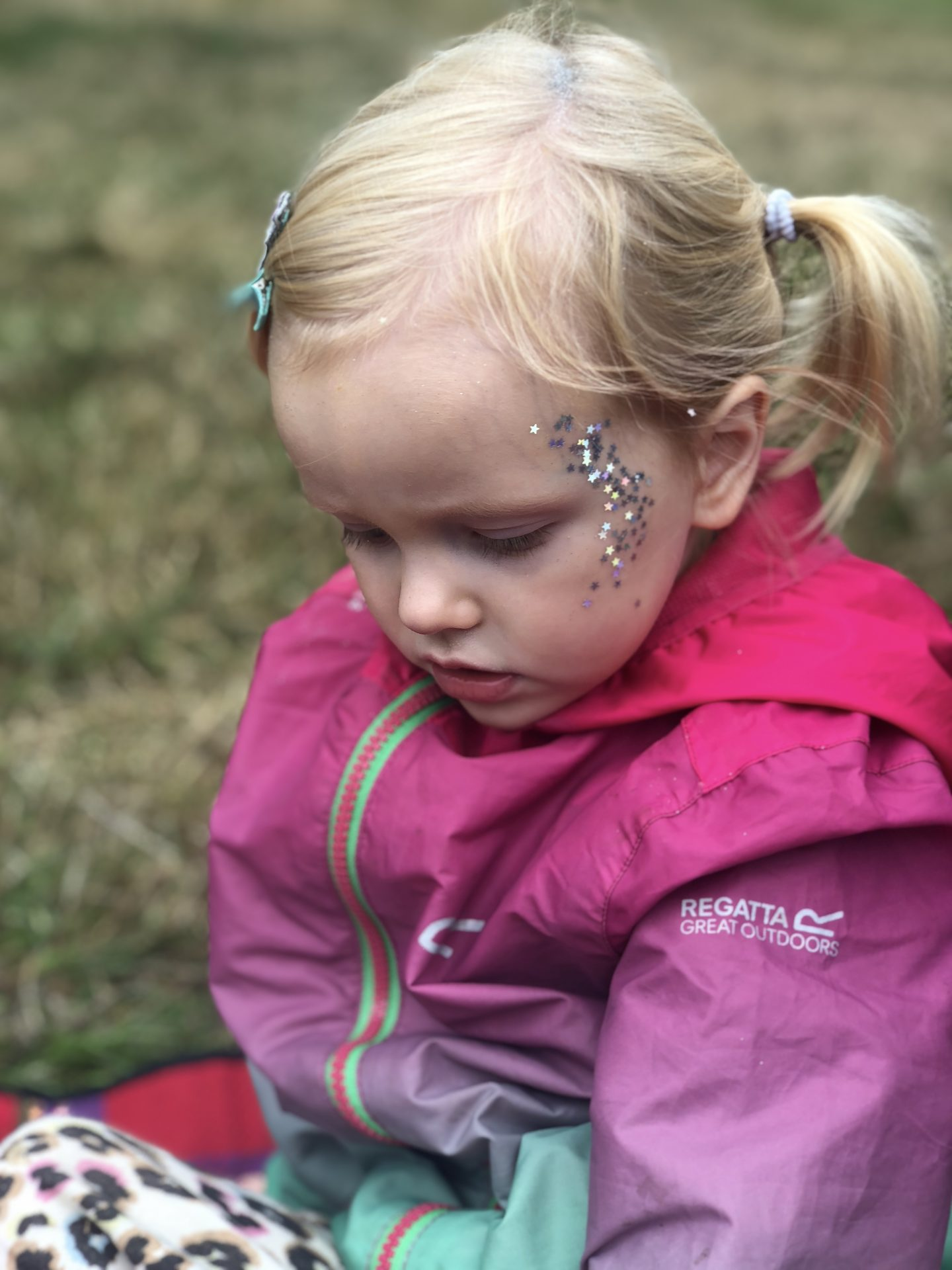 A blonde girl is wearing a waterproof rain jacket and has silver stars on her face.