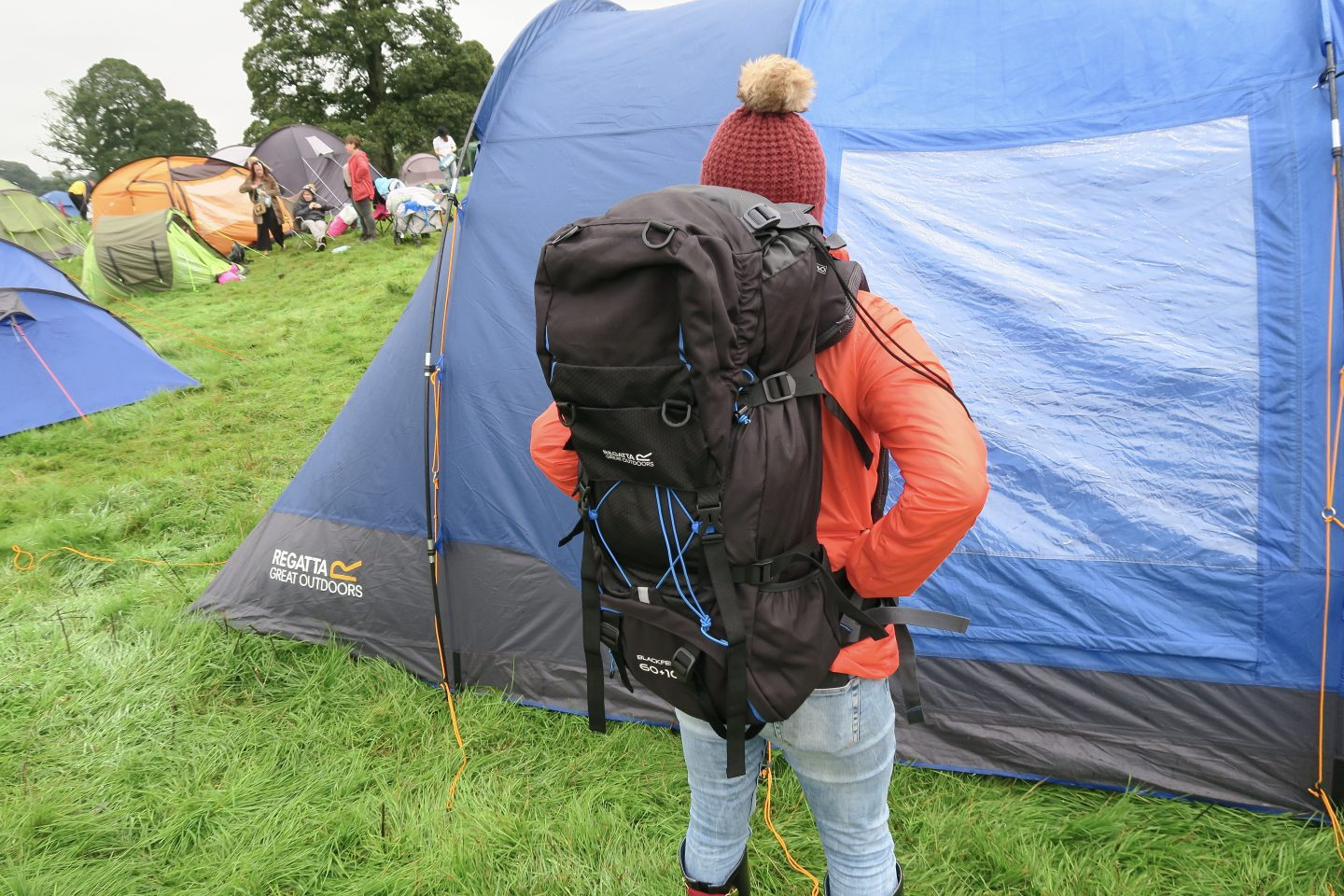 A woman wears a camping rucksack in front of her tent at a festival.