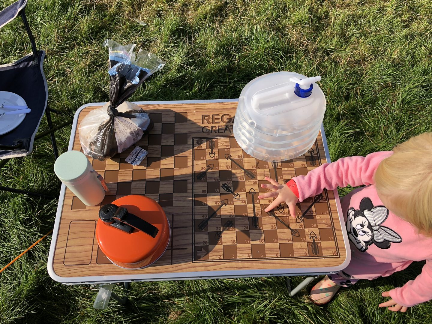 A toddler plays with the checkerboard on a camping games table. The table is on the grass and has a kettle and water canteen on it.