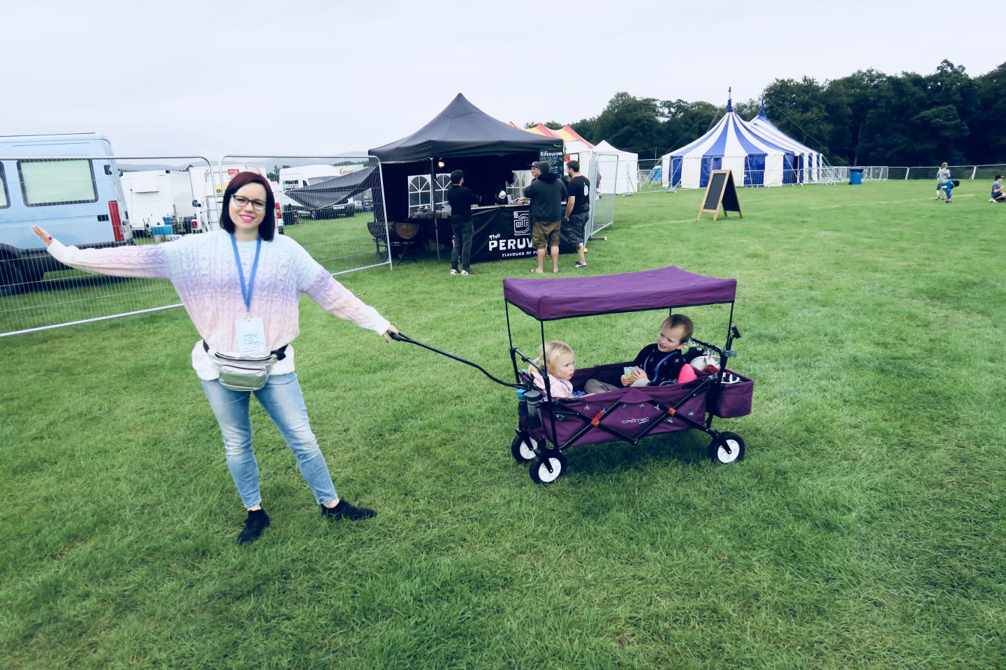 Woman pulling a wagon with kids inside it at a festival.