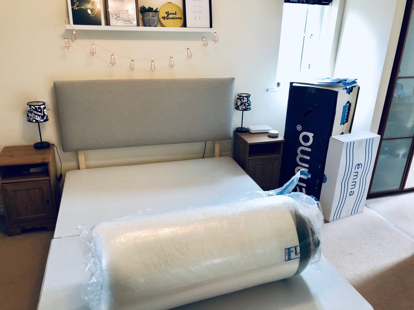 A bed with the Emma Mattress taken out of its box but still in its plastic wrapping.